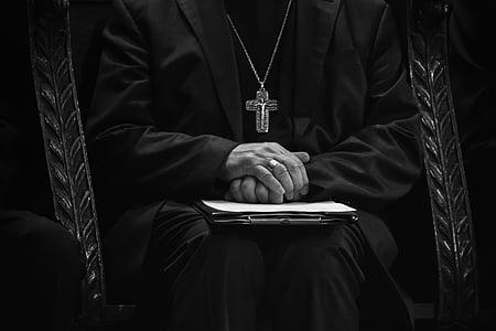 man wearing in black wearing gold cross necklace