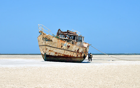 photo of white and brown ship on sand