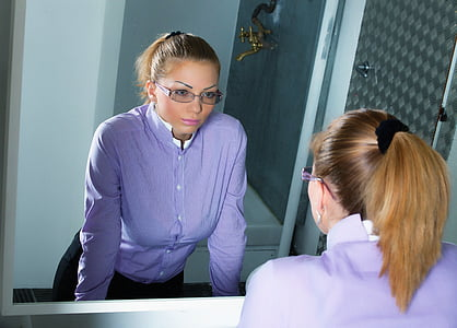 woman looking her reflection in mirror