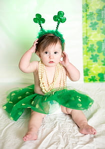 toddler wearing green tutu skirt and yellow necklace