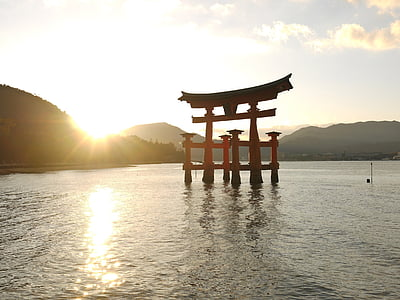 red wooden arch on calm body of water during golden hour
