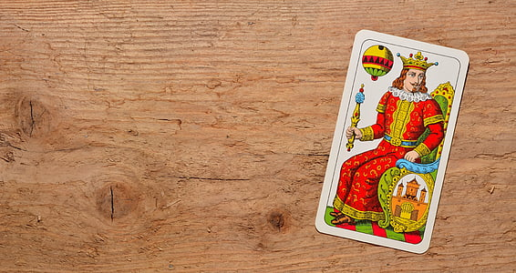 flat-lay photo of red and yellow dressed king card on brown desk