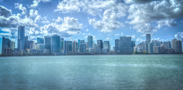 blue body of water near high rise buildings under clouds at daytime