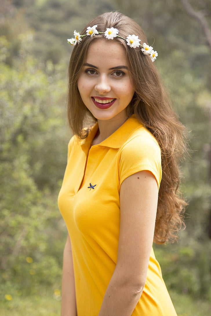 woman wearing yellow polo shirt and flower crown