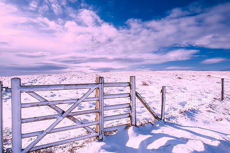 white sand with fence under cloudy sky