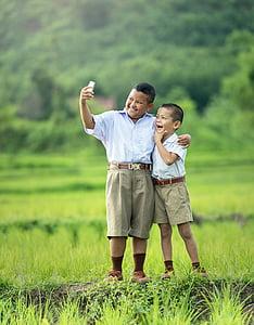 two boys wearing school uniform in the middle of field