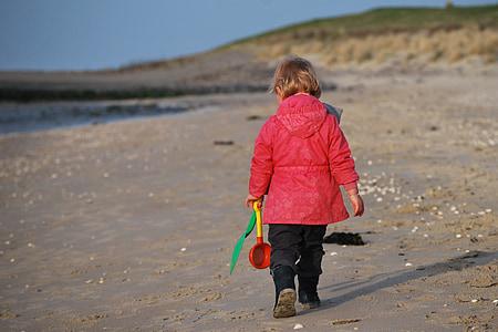 photo of girl walking on seashore