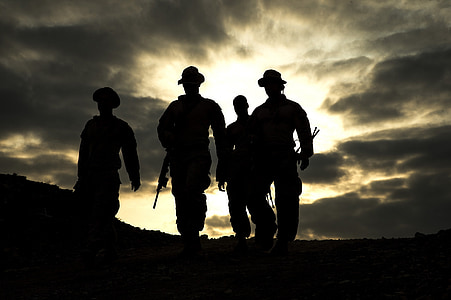 silhouette photo of four man walking on pathway carrying weapons