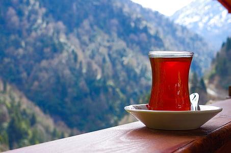 clear Turkish tea glass on brown board