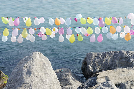 balloon buntings over stone edge and ocean during day