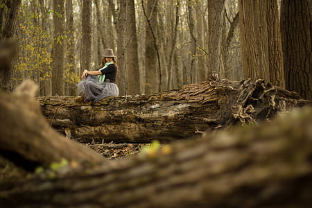 woman sitting on tree trunk at the middle of forest