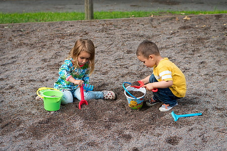 two child playing on sand