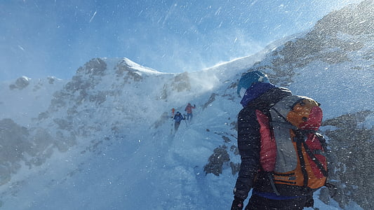 people climbing on snow capped mountain during daytime