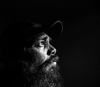 man with black beard wearing black cap on grayscale photography