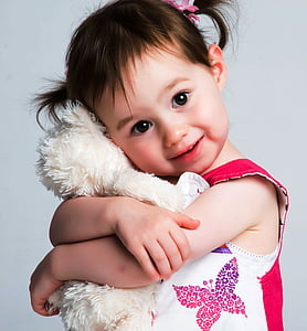 toddler wearing red top hugging white plush toy