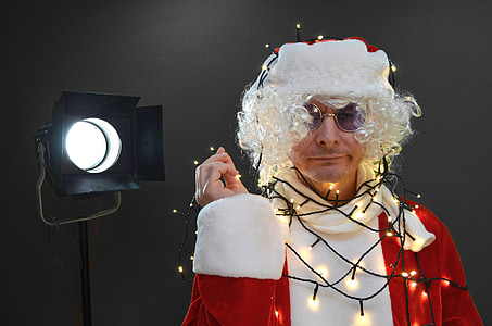 man wearing Santa Claus with string lights near black studio lamp