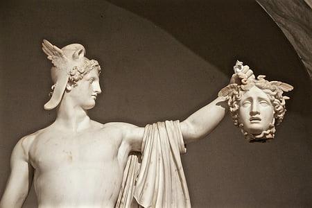 white concrete man holding head of woman statue