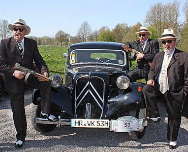 three men standing beside black vehicle