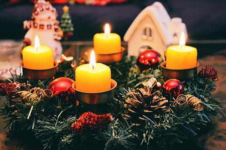 four yellow votive candles under green garland wreath