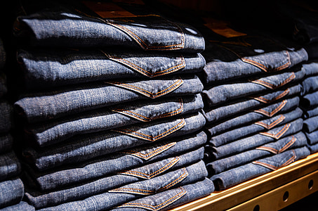 blue denim bottoms on brown wooden rack