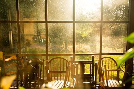 brown wooden Windsor chair near clear glass window