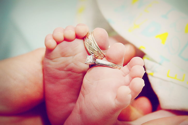 baby's feet with two silver-colored rings