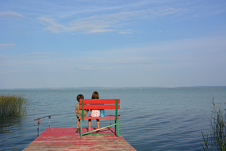 two children sitting on red and green wooden bench on bridge