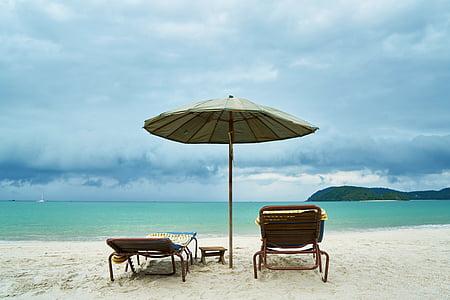 gray parasol near two sun loungers in shoreline near body of water