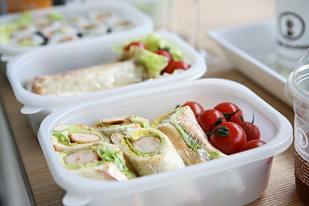 two white plastic containers with sandwich and tomatoes