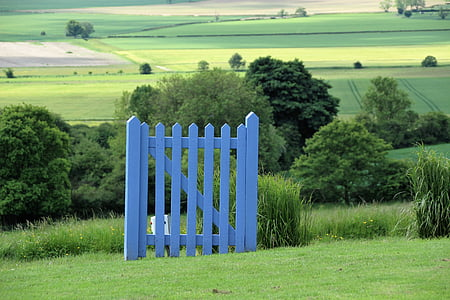 blue wooden fence on grass field during daytime