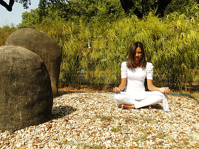woman meditating surrounded with green trees