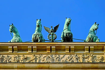 four gray concrete horse statues on roof
