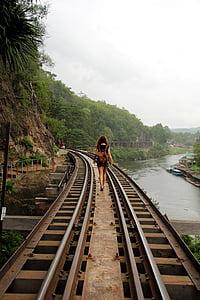 woman waling on brown metal rail road during daytime