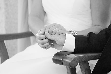 grayscale photography of groom and bride holding their hands together