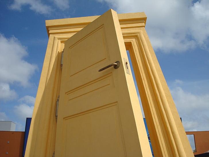 yellow wooden door under cloudy sky during daytime