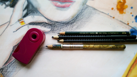 four pencils near red sharpener on canvas