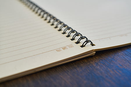 opened spring bounded notebook on brown surface
