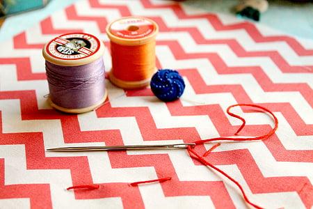 two thread spools near white knitting pin