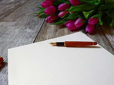 red fountain pen near bouquet of pink tulips