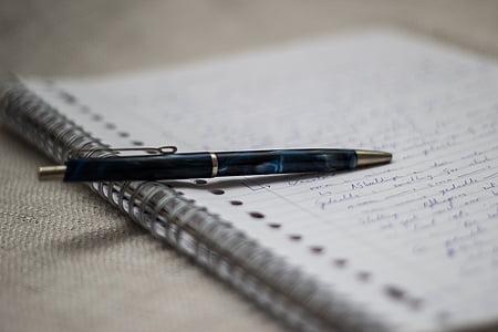 black retractable pen on spiral notebook