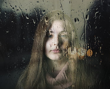 closeup photography of woman behind wet glass