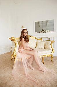 woman in nude-colored mesh dress sitting on sofa