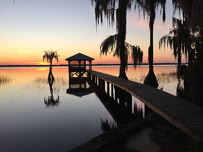 dock on body of water during sun set