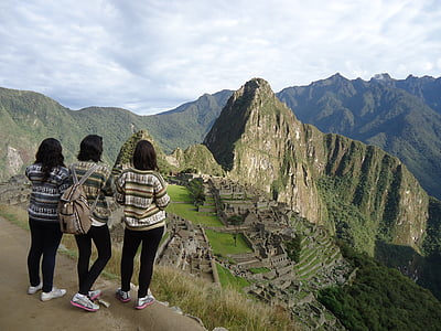 three women standing while looking at mountain range