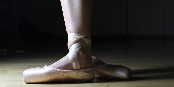 photo of ballerina on beige parquet floor