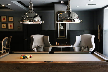 two silver-colored pool lamp and brown pool table