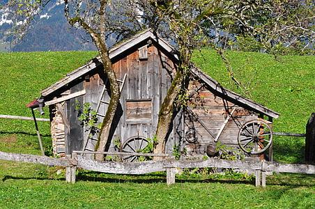 brown wooden barn around green grass field