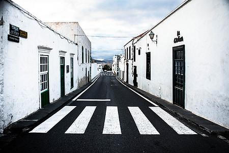 black asphalt road between white painted buildings