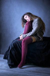 woman wearing gray sweater and pair of purple socks sitting on black mattress