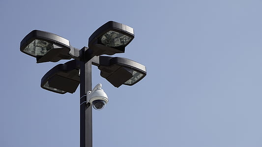 white surveillance camera mounted on black post